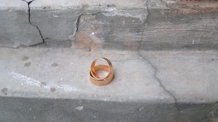 rock wall : Wedding rings stand on a concrete surface