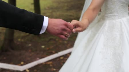 новобрачный : Beautiful young woman bride holds the hand of a man in outdoors. Follow me