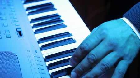 akord : Closeup of male hands playing digital piano.