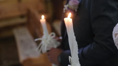 nişanlısı : A closeup of high yellow candles held by newlyweds during the wedding ceremony