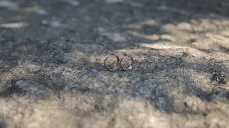 casar : Gold ring lie on the stone surface in sunny day Vídeos