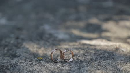 personalizado : Gold ring lie on the stone surface in sunny day Vídeos