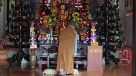 кхмерский : a view of a buddhist monk with orange robe pray in temple 30 July, Nha Trang, Vietnam