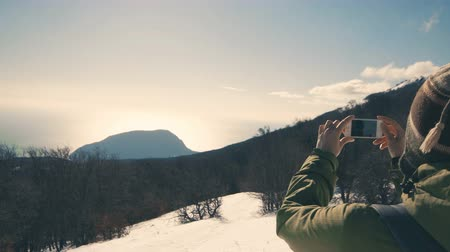 hora : Hiker,girl taking picture of wild winter nature with her smartphone, 4k Stock Footage