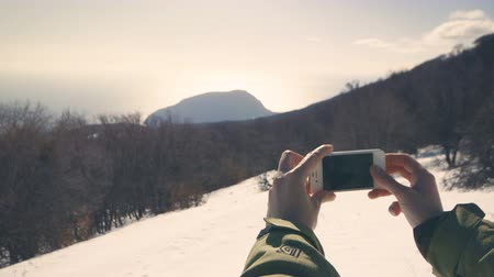hora : Hiker taking picture of wild winter nature with her smartphone
