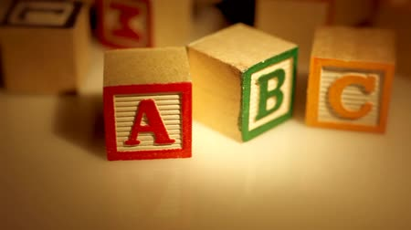 blocos : Close-up macro with warm spotlight shot of wooden ABC learning blocks for children. Seamless looping video.-