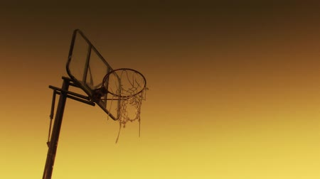 abroncs : Upward POV of solitary basketball hoop at sunset. Shot on 3CCD HD 1080p.-