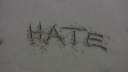sinir : The word HATE written in the sand, water rushes over and washes it away. Shot on HDV 1080.-