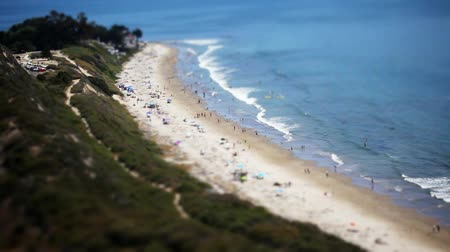 фокус : Beautiful wide shot of people enjoying a sunny day at the beach. This is a Tilt Shift shot so the foreground and background are out of focus and the center area of the shot is in focus. Makes for a very dramatic and cool effect. Shot on HD 1080P.- Стоковые видеозаписи