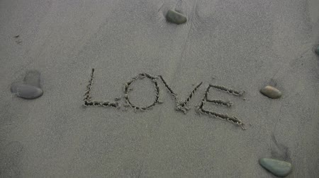 miłość : The word LOVE written in the sand, water rushes over and washes it away. Shot on HD 1080.- Wideo