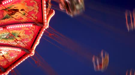 kolotoč : View looking up at the carousel swing ride. Carnival Midway.-