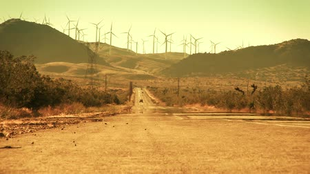 turbine : Long shot of a hot desert road and wind turbines on the mountains in the background. Shot on 4:2:2 Canon HD 1080p.