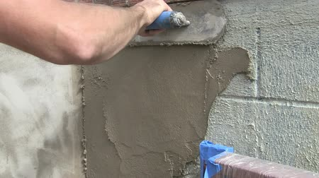 sıva : Close-up video of man putting stucco on a cinder block wall. Stok Video