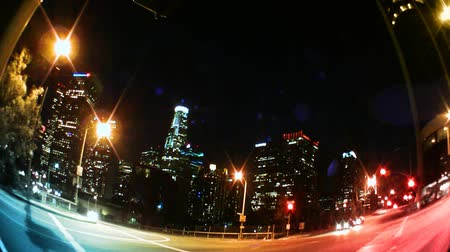 ügy : Los Angeles Skyline at night with traffic streaking by, city buildings and lights.-