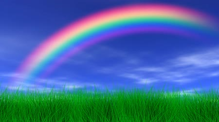 arco íris : Rainbow, blue sky, light clouds, slight breeze and lush green grass. Seamless looping video animation.-