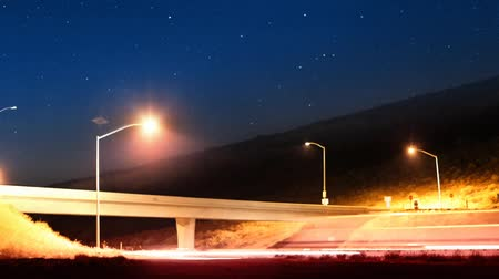 camionagem : frame time-lapse of traffic driving past on freeway at night.