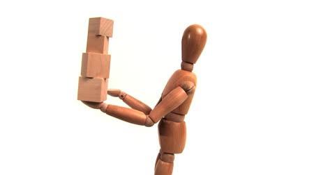 manekin : Wooden mannequin holding wooden blocks in one hand only. Shot on 3CCD HD 1080. Seamless looping clip.- Wideo