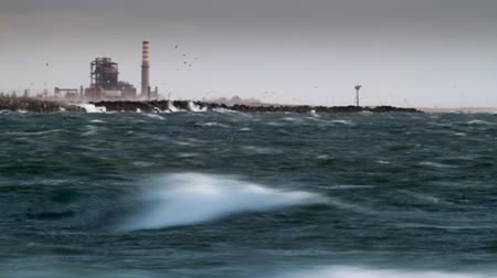 fırtına : Long telephoto shot of waves crashing against jetty with abstract industrial complex in the distance.-