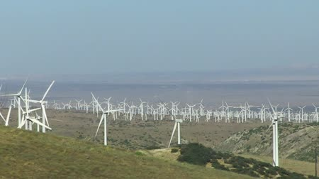 anahtar kelimeler : Spinning wind turbines on green hills and clear blue sky. Cars driving by on road. Shot on  HD 1080p 4:2:2.