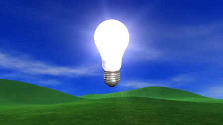 efektywność : V.10 - Old style light bulb explodes to reveal new energy saving light bulb, over blue sky, light clouds, slight breeze and lush green grassy hills. HD seamless looping video animation.-