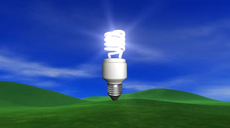 солнечный : V.9 - Sun bursts to reveal energy saving light bulb. Blue sky, light clouds, slight breeze and lush green grassy hills. HD seamless looping video animation.-