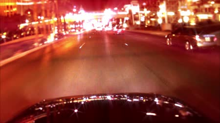 night scene : Car mounted camera POV of sparkling city lights reflecting off the hood of a car.