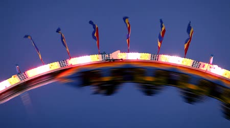 bulanık : Night shot of people riding the roller-coaster ride at the carnival midway.- Stok Video