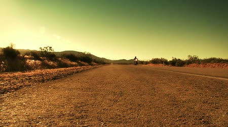 motocykl : Low POV shot of motorcycle riding by on a road desert road. Shot on 4:2:2 HD 1080p.