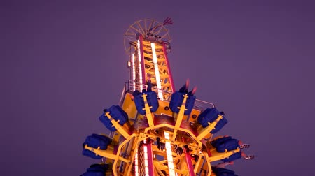 People ride to the top of the sky drop before plummeting back down. Ambient audio included.-
