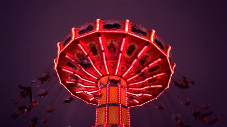 kolotoč : View looking up at the carousel swing ride. Carnival Midway at night.-