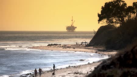 natura : People walk along beach with large Pacific Ocean oil rig drilling platform in the distance. Off the coast of California. Circa 2009.  Shot on HD 1080P.- Wideo