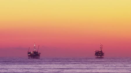 oliwa : Sun setting on the Pacific Ocean, oil rig drilling platforms on the horizon. Circa 2010.- Wideo