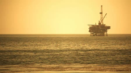 sunset sea : Large Pacific Ocean oil rig drilling platform off the coast of California. Circa 2009. Shot on HD 1080P.- Stock Footage