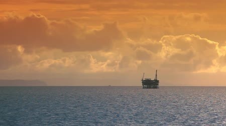 sunset sea : Sun setting on the Pacific Ocean, oil rig drilling platform on the horizon. Circa 2010.-
