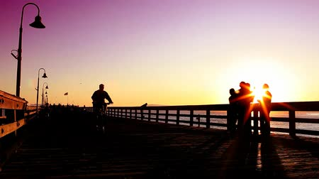 bisiklete binme : Silhouette of people riding bikes, walking and hanging out on the pier at sunset.- Stok Video