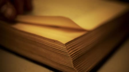 régi : Close-up macro shot of person turning pages of an old book, all text is out of focus in the background, corner edge of book in foreground in focus. Shot on - HD at 1920x1080 30p.-