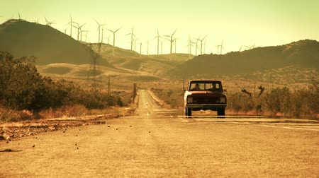teherautó : Long shot of an old truck driving down a hot desert road with wind turbines on the mountains in the background. Shot on 4:2:2 HD 1080p.