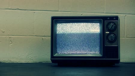 broadcast video : Old generic tv with static sitting on floor against an industrial block wall. Shot on HD 1080p.- Stock Footage
