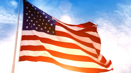 bandeira americana : Beautiful glowing footage of the American Flag flowing in the wind with a golden sunset in the background and a blue sky with white puffy clouds.- Vídeos