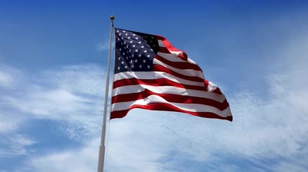 Beautiful glowing footage of the American Flag flowing in the wind with a blue sky with white puffy clouds. HD 1080P.-