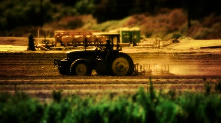 talaj : Silhouette shot of tractor plowing a field in the late afternoon. Shallow depth of focus on tractor.- Stock mozgókép