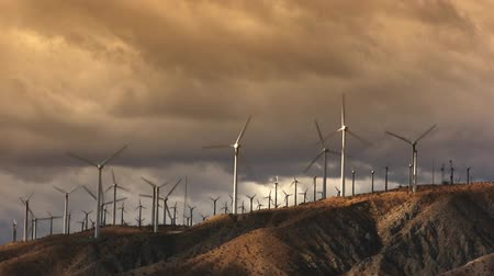 turbine : Spinning wind turbines with a orange cloudy sky, clouds and brush. Shot on HD 1080p.- Stock Footage