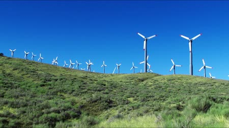 turbine : Spinning wind turbines on green hills and clear blue sky. Shot on HD 1080p. Stock Footage