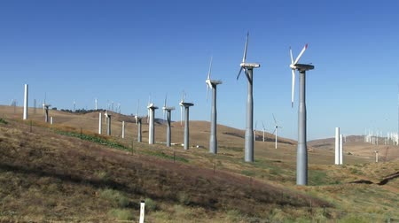 anahtar kelimeler : Spinning wind turbines with traffic in the foreground and clear blue sky. Shot on 422 HD 1080p.
