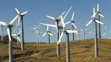 turbine : Spinning wind turbines on hills and clear blue sky. Shot on HD 1080p.