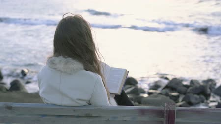 A young girl sits on a bench by the sea reads a book at sunset of the evening day. 4K. A child reading on the beach at sunset. A girl relaxing by the sea, coastline.
