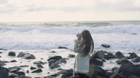 Girl photographer on the shore of the stormy sea makes pictures. Tourist traveler photographer making pictures ocean. Stormy sea with storm clouds. Snapshots of a trip to the sea.4k.30fps. Dostupné videozáznamy