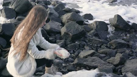 Young woman in an elegant coat walks on the beach. The girl enjoys a warm autumn day. Portrait of a beautiful girl near the water. Blowing the sea foam from your hands .4k.30fps