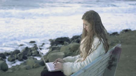 Young beautiful girl sitting at a table with a laptop on the beach prints 4k,30fps
