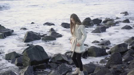 Young woman in elegant coat walks on the beach. The girl is enjoying the warm autumn day. Portrait of beautiful girl near the water.4k.30fps